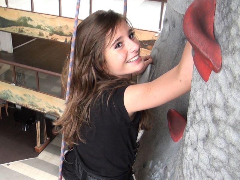 Adolescente sur un mur d'escalade intérieur en colonie de vacances à Courchevel