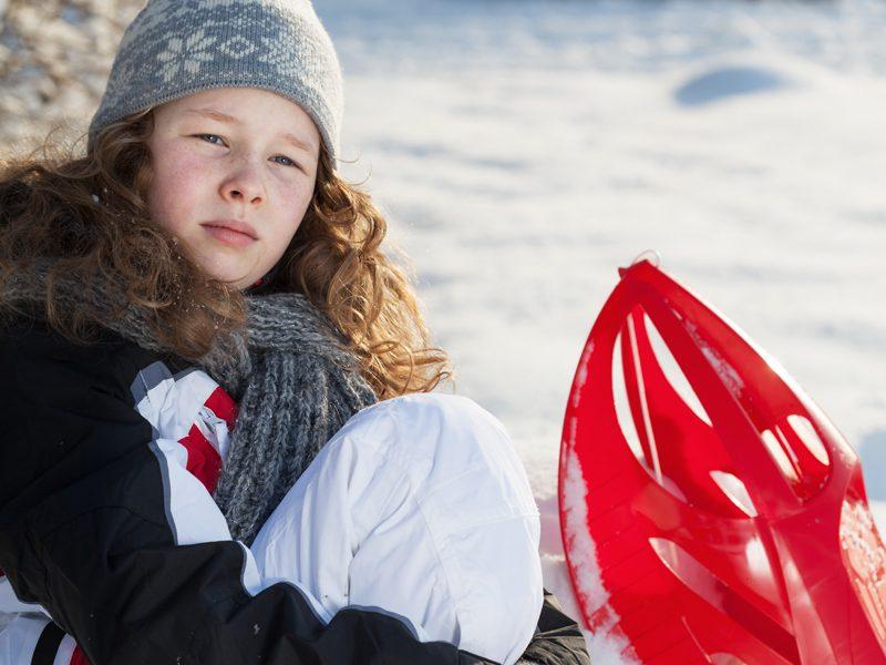Jeune fille à luge sur la neige