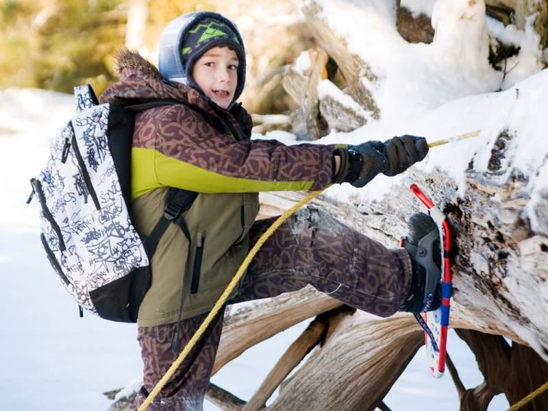 Enfant en raquette à neige en colonie de vacances