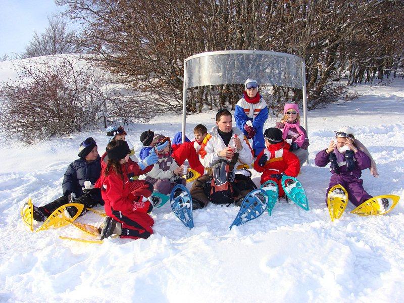 Groupe d'enfants assis dans la neige en colonie de vacances