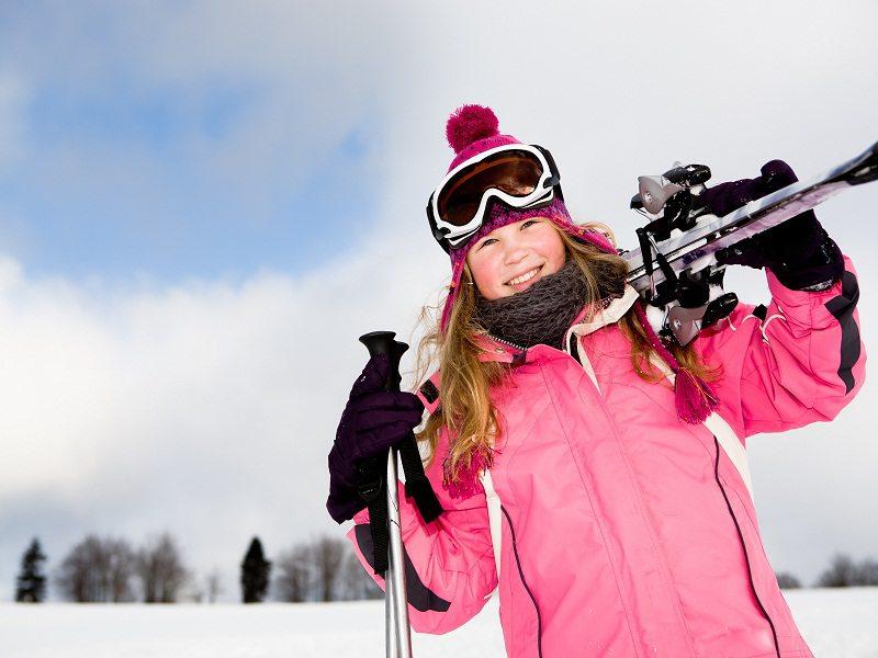 Jeune fille avec ses skis sur les pistes