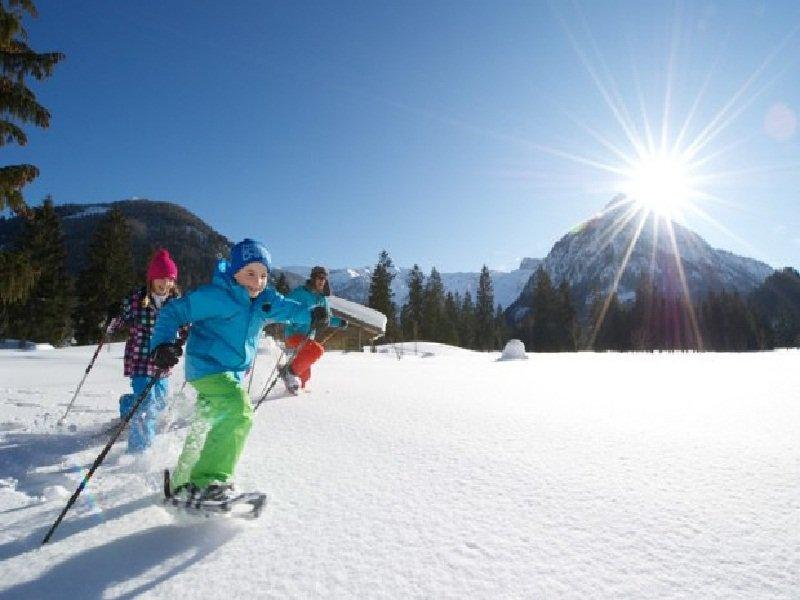 Enfants se déplaçant en raquettes dans la neige en colo