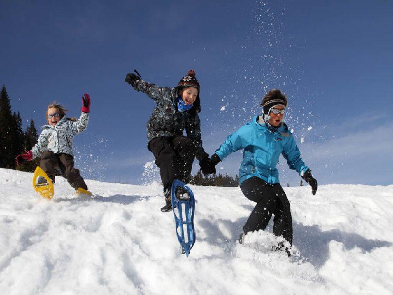Enfants courant dans la neige en raquettes