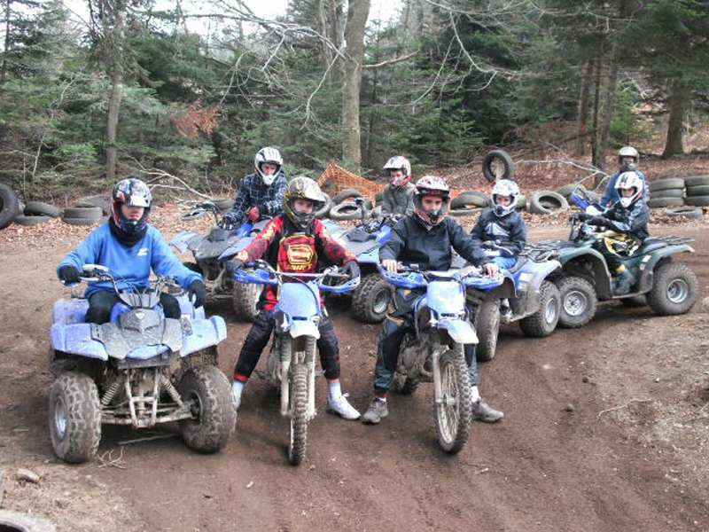 Groupe d'enfants conduisant quad et moto