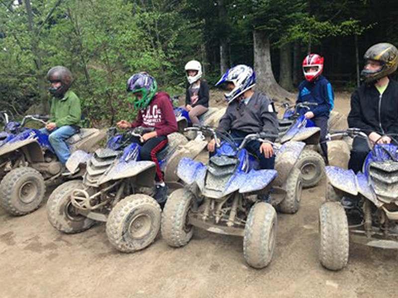 Groupe d'enfants en colonie de vacances conduisant un quad