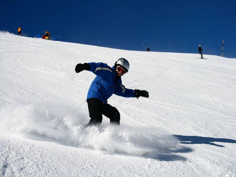 Adolescent en descente en snowboard sur les pistes de Courchevel