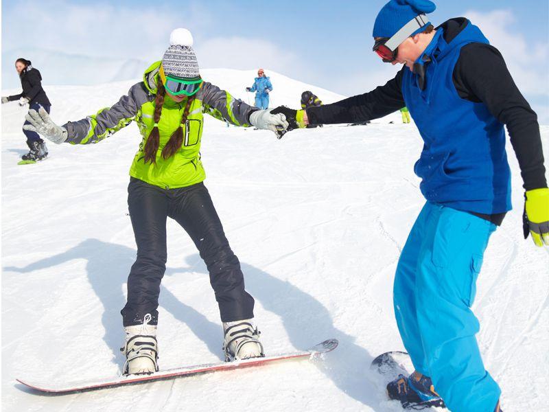 ados apprenant à faire du snowboard en colonie de vacances cet hiver