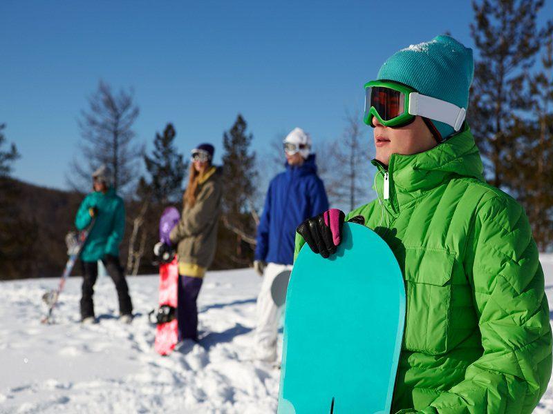 Ados avec leur planche de snow en colonie de vacances à Courchevel l'hiver