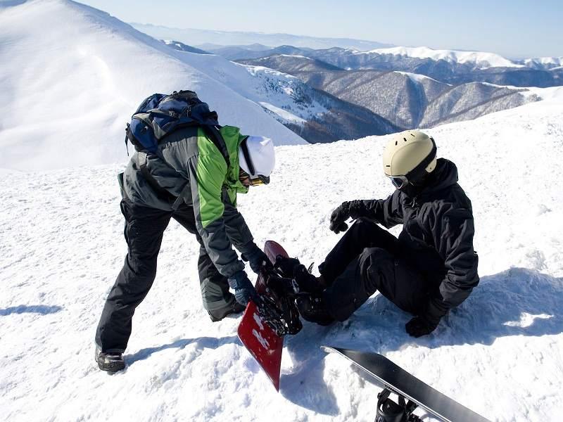 ado aidant son ami à chausser son snowboard en colo à courchevel cet hiver