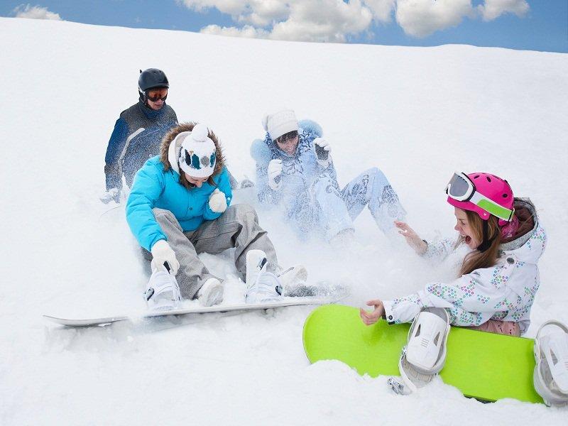 adolescents jouant dans la neige cet hiver pendant une colo de snowboard