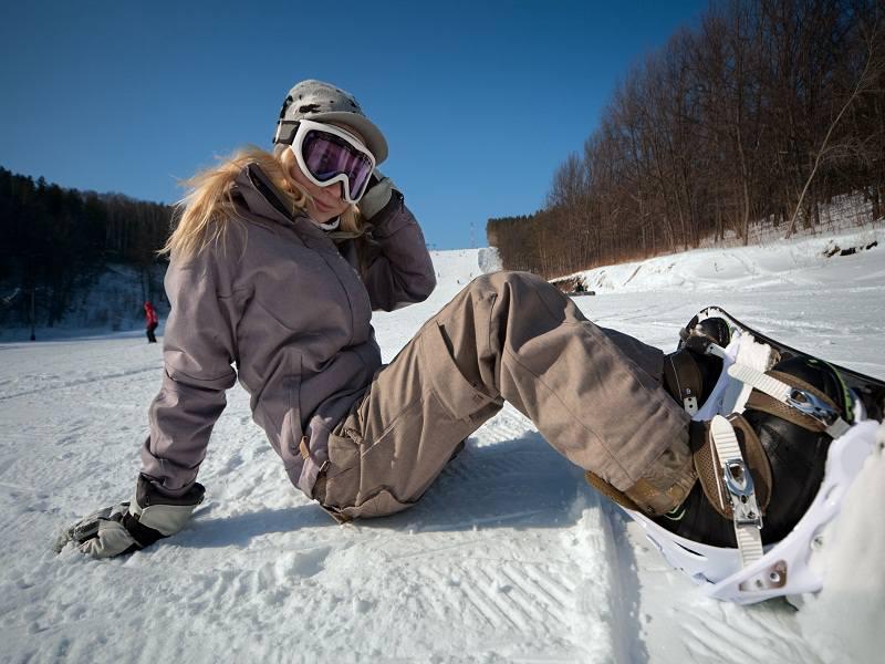 ado assise dans la neige faisant du snowboard cet hiver en colonie de vacances