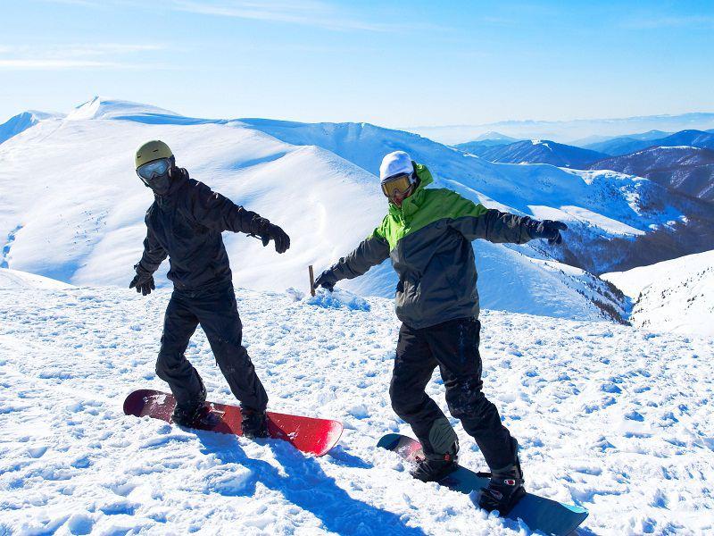 Deux ados faisant du snowboard en colonie de vacances d'hiver