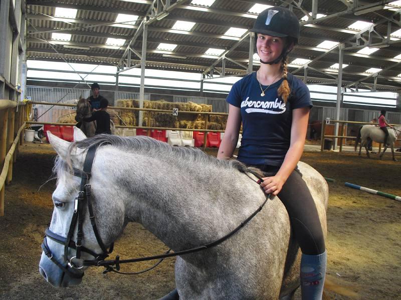 Jeune fille montant à cheval en manège