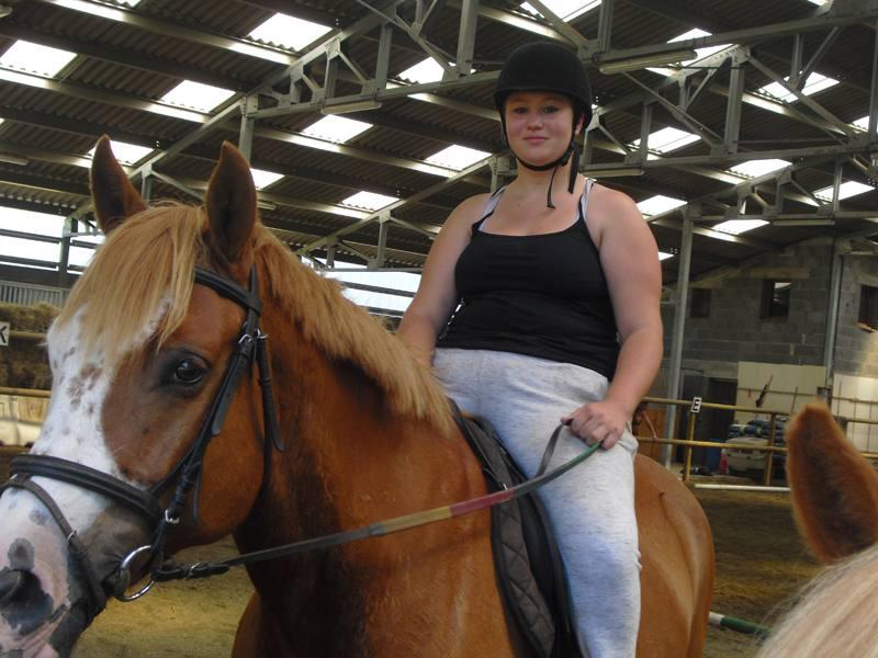 Jeune ado sur le dos de son cheval en colonie de vacances