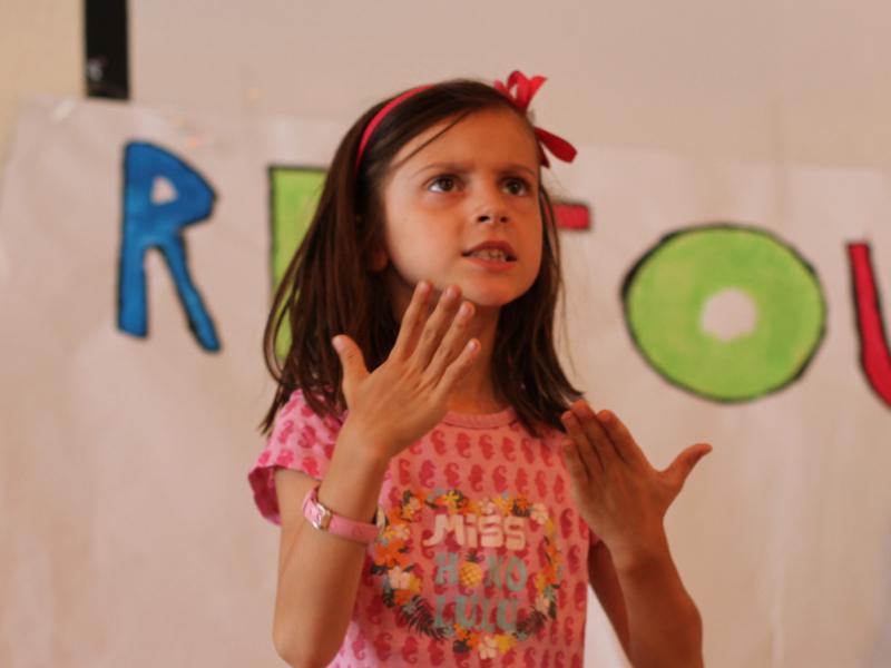 Enfant en train de jouer une scène en théâtre