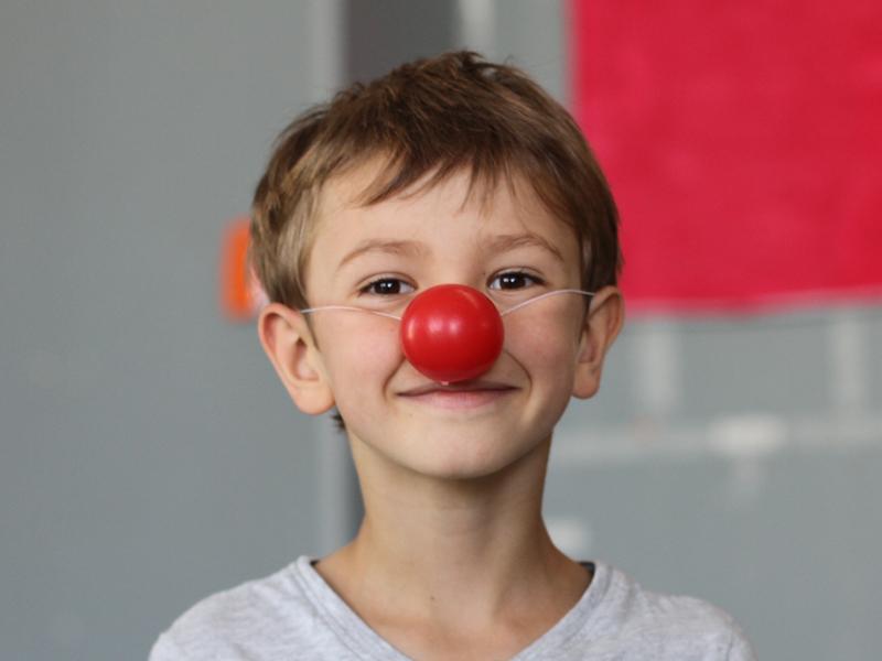 Jeune garçon portant un nez rouge de clown