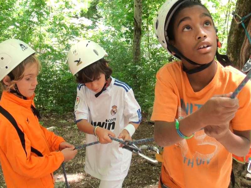 Enfants pratiquant le rappel d'escalade en colonie de vacances