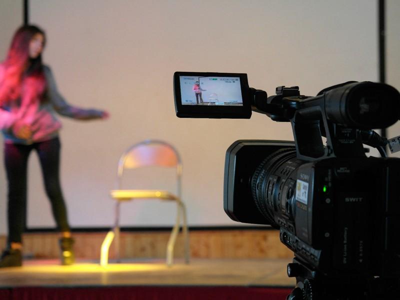 gros plan sur une caméra filmant une pièce de théâtre en colo