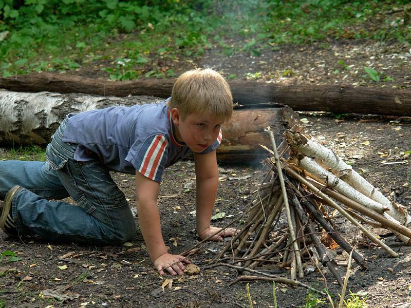 Petit garçon en train d'observer un feu de camp