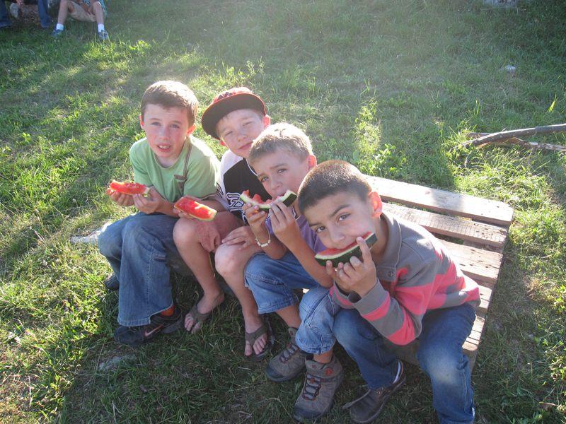 Groupe d'enfants assis sur une palette en train de manger de la pastèque