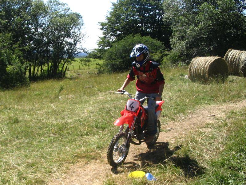 Enfant de 12 ans apprenant à conduire une moto cross en colonie de vacances