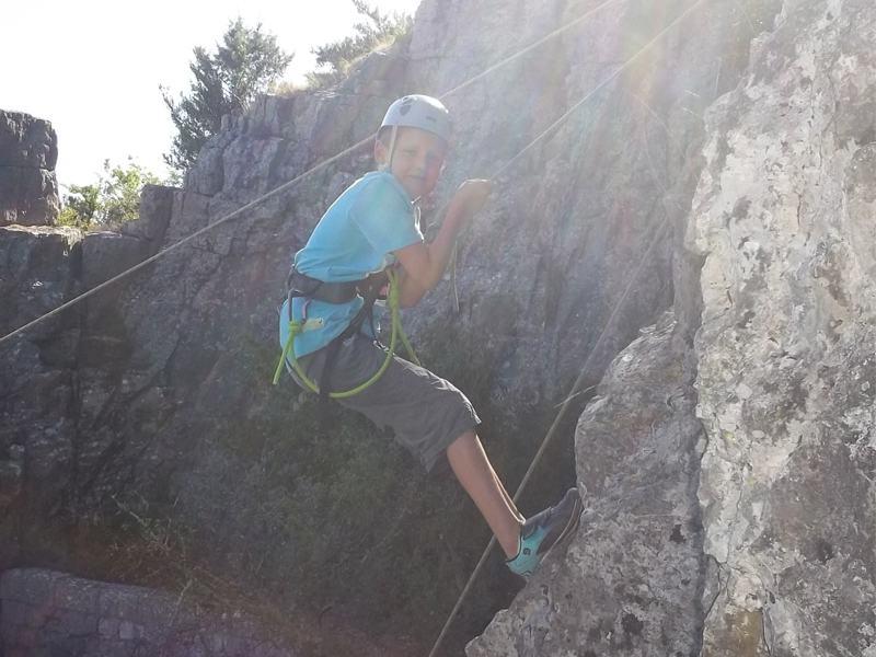 Enfant sur un mur d'escalade en colonie de vacances