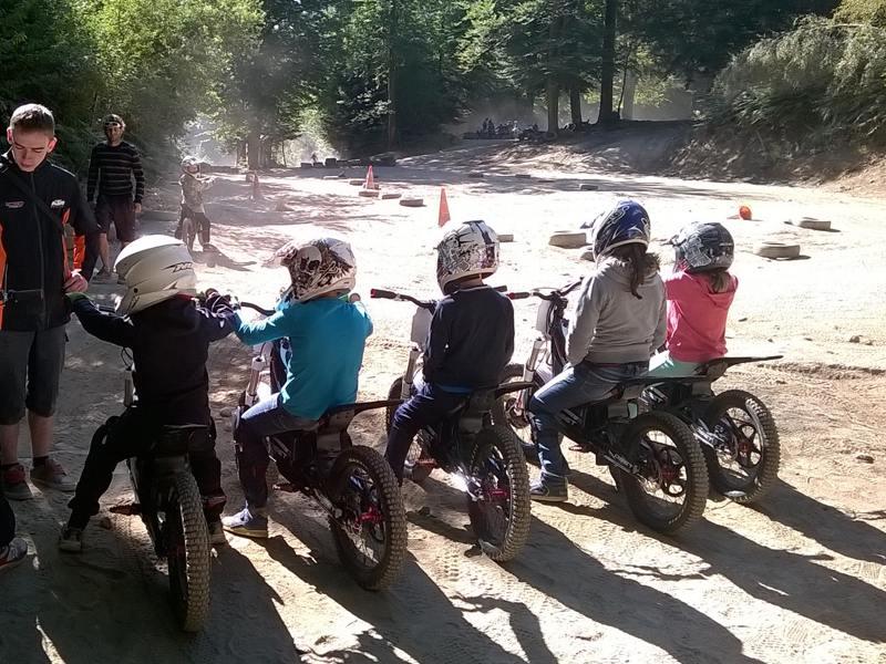 Animateur apprenant aux enfants à faire de la moto en colo