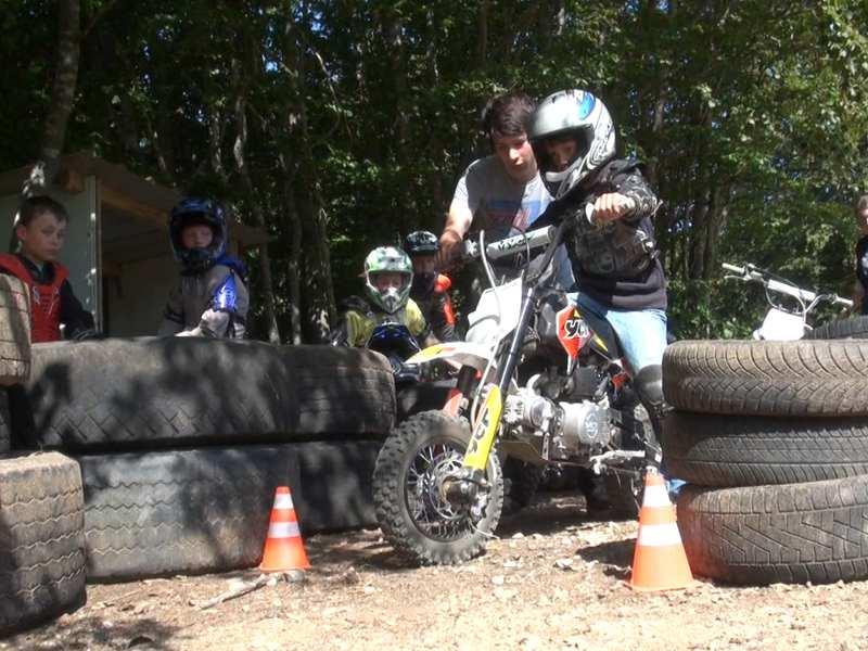 Enfant apprenant à faire de la moto sur terrain de moto cross en colo
