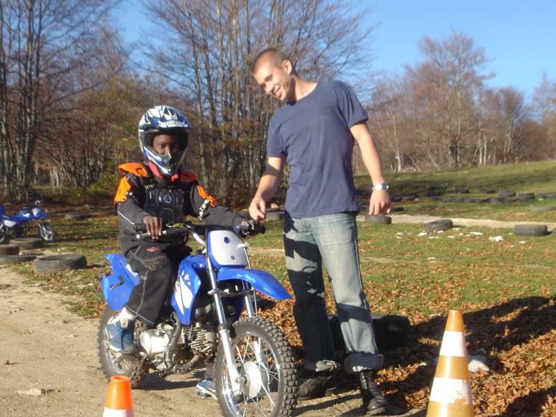Enfant apprenant à conduire une moto cross en colo