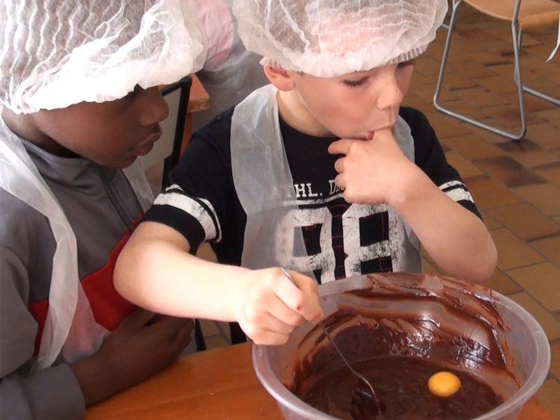 Enfant de 8 ans apprenant à cuisiner en colonie de vacances