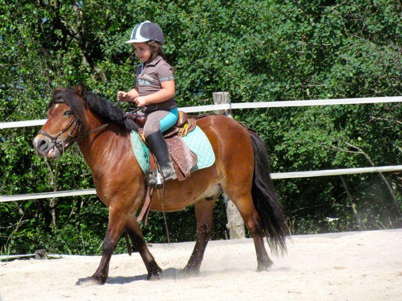 Enfant de 9 ans sur un poney en colo