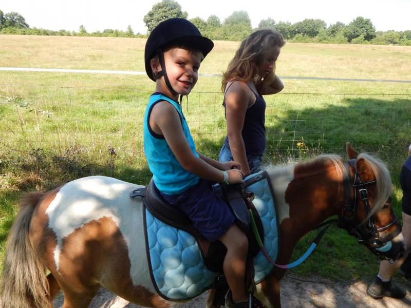 Enfant faisant du poney en colo