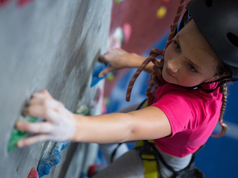 Vue sur une jeune fille qui grimpe un mur d'escalade à Monistrol lors d'une colonie de vacances Quad et Cross