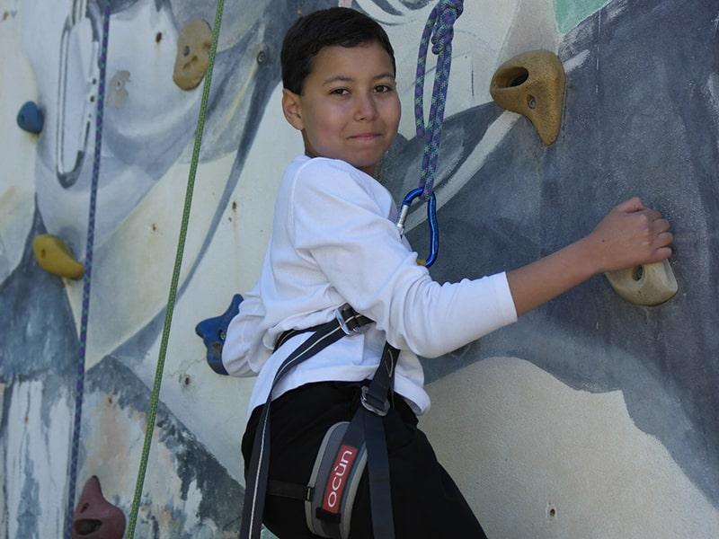 Jeune garçon en colo de vacances qui s'apprête à grimper le mur d'escalade à Monistrol lors de son séjour Quad et Cross