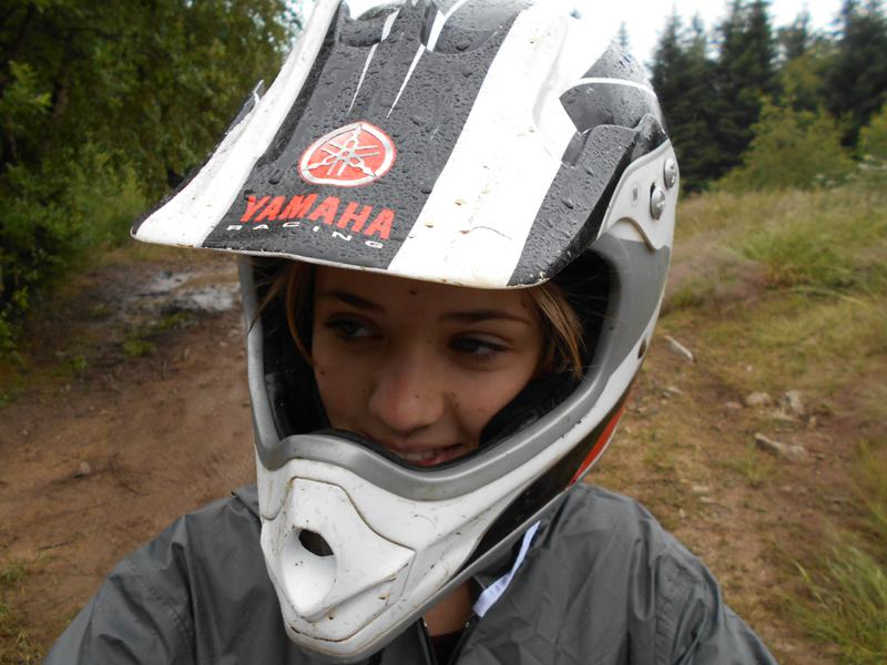 Portrait d'une adolescente en colo avec casque de moto cross et quad