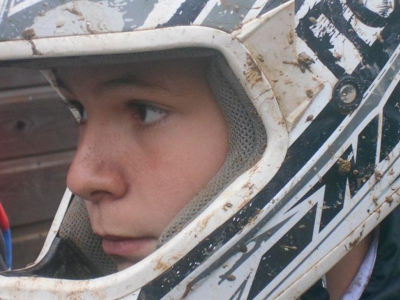 Portrait d'un jeune en colo portant un casque de moto