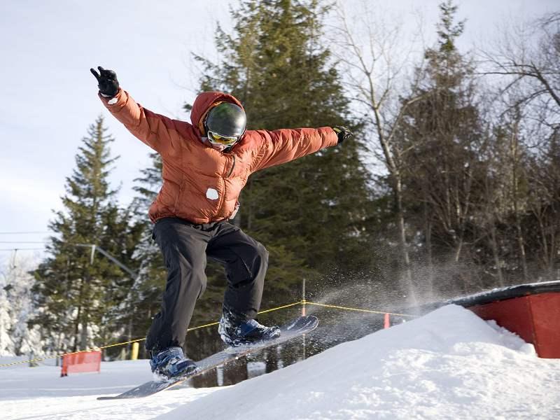 Enfant pratiquant le snowboard en colonie de vacances à Courchevel