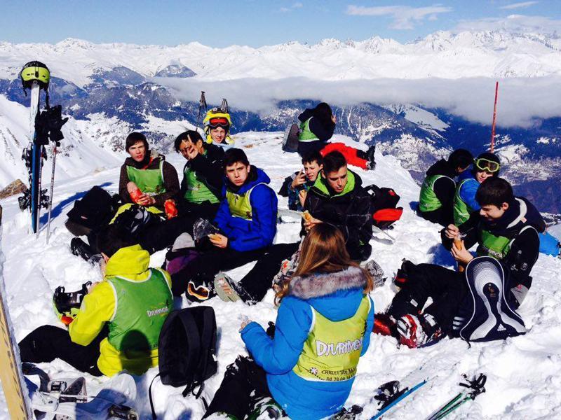 Groupe d'ados à la montagne sur les pistes de ski