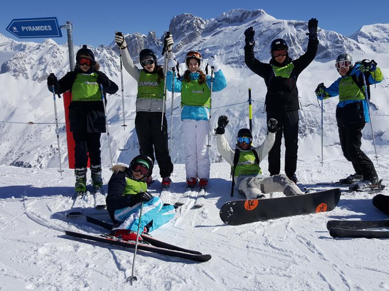 Groupe d'enfants pratiquant divers sports d'hiver en colo