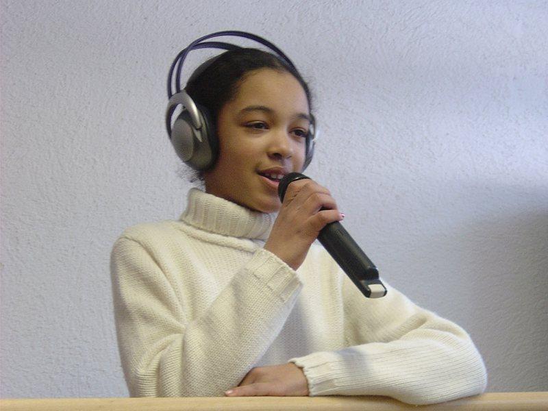 jeune fille avec un casque de musique et un micro apprenant à chanter