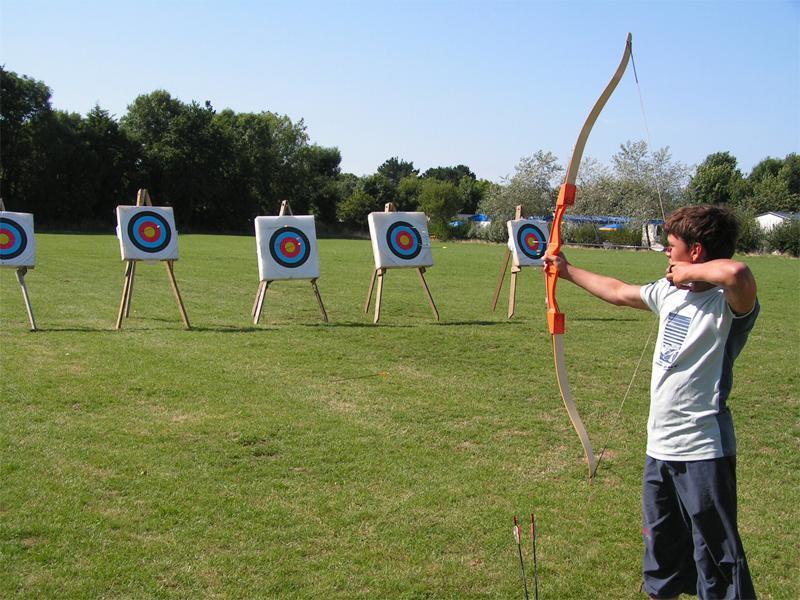 enfant apprenant à faire du tir à l'arc en colo de printemps