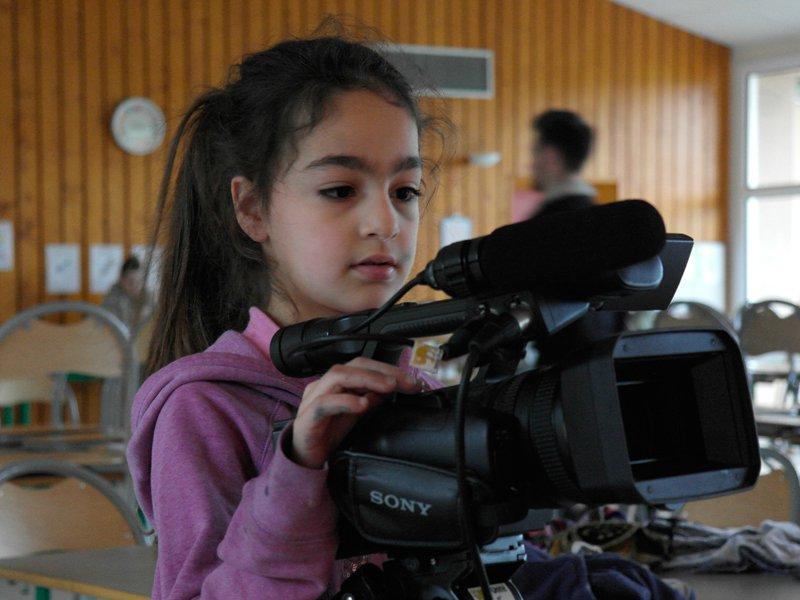 Fillette apprenant à filmer en colonie de vacances artistique