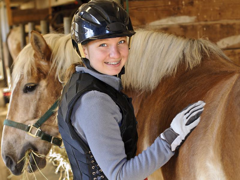 Adolescente brosse son cheval en colonie de vacances