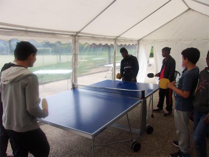 enfants et ados jouant au ping pong en colo