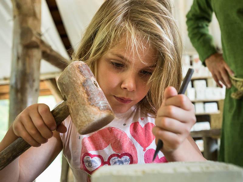 fillette apprenant à tailler la pierre en colo médiévale cet été