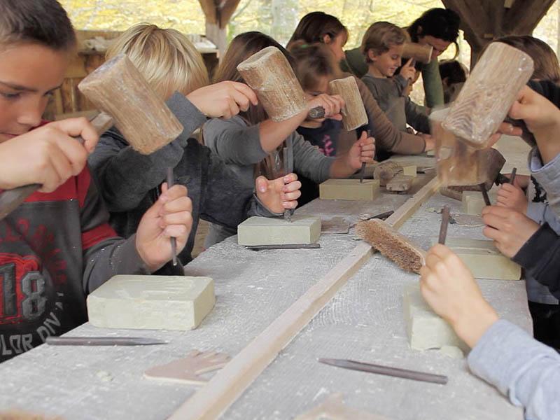 Enfants apprenant à tailler la pierre comme au moyen age en colonie