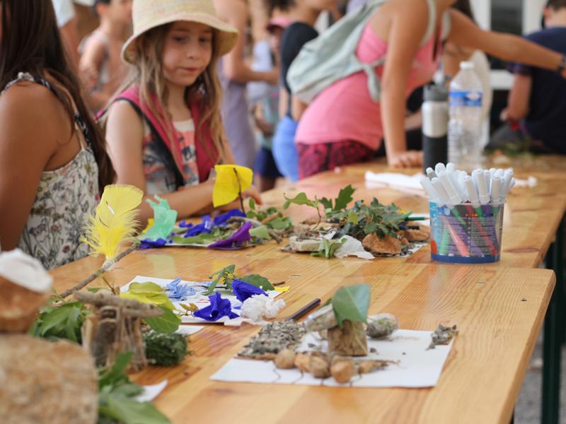 enfants faisant des activités manuelles et artistiques en colonie de vacances ce printemps