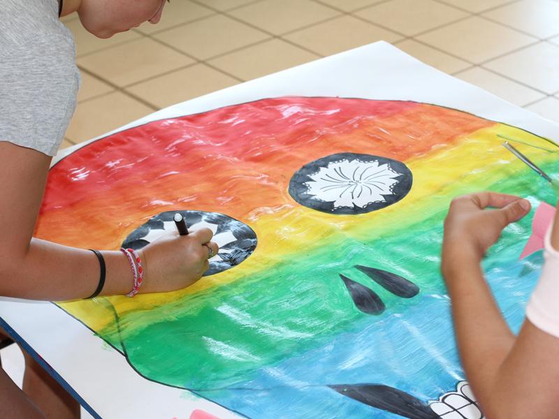 Enfants faisant une fresque colorée en colonie de vacances artistiques