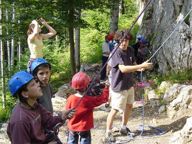 groupe d'enfants faisant de l'escalade et de la descente en rappel en colo
