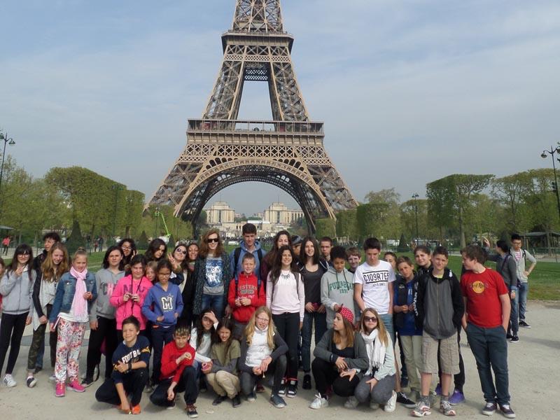 Groupe d'enfants et ados posant devant la tour eiffel lors d'une colonie de vacances au printemps